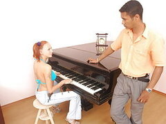 Fiery redhead girl Tira seduces her caramel-skinned piano lesson teacher. She begins the fun by pulling his cock out and sucking it like a naughty nympho. The surprised guy doesn't stop her and soon shoves his big cock into her pussy. This turns out to be